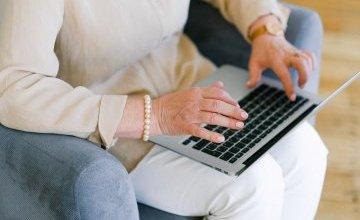 Zdjęcie przedstawiające kobietę piszącą na laptopie.